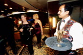 Waiters serving passengers with drinks. P&O cruises Ship Aurora, a 76,000 ton cruiser in dock. It can carry 1800 passengers. Southampton. The crew is mostly Indoneasian. - Paul Box - 14-05-2002