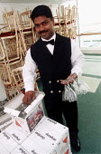 Steward unpacking wine glasses. P&O cruises Ship Aurora, a 76,000 ton cruiser in dock. It can carry 1800 passengers. Southampton. The crew is mostly Indoneasian. - Paul Box - 14-05-2002