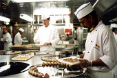 Chef and catering assistants in the galley preparing food. P&O cruises Ship Aurora, a 76,000 ton cruiser in dock. It can carry 1800 passengers. Southampton. The crew is mostly Indoneasian. - Paul Box - 14-05-2002