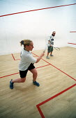 Competitors playing squash. Axa Sun Life. Bristol. - Paul Box - 2000s,2002,cardio vascular,Cardiovascular,centre,cities,city,club,clubs,COMPETITATIVE,Competition,Competitive,Competitor,exercise,exercises,exercising,FEMALE,fit,fitness,game,games,get,getting,health,