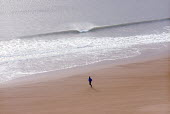 Jogging along Tenby beach, Pembrokeshire. South Wales. - Paul Box - 2000s,2002,adult,adults,beach,BEACHES,coast,coastal,coasts,country,countryside,couple,COUPLES,ENI environmental issues,exercise,exercises,holiday,holiday maker,holiday makers,holidaymaker,holidaymaker