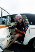 Dame Edna Everage arriving by Roll Royce car. Bristol. - Paul Box - 1980s,1984,ACE entertainment,ARRIVAL,arrivals,arrive,arrived,arrives,arriving,barry,cities,city,Comedian,Comedians,Comedy,cross,cross dressing,drag,dress,dresser,dressers,dressing up,entertainer,enter