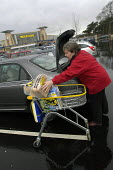 A lady loads her car with her shopping Morrisons supermarket, Cribbs Causeway, Bristol. - Paul Box - 2000s,2004,AUTO,AUTOMOBILE,AUTOMOBILES,AUTOMOTIVE,bag,bags,boot,bought,buy,buyer,buyers,buying,car,car park,car parks,cars,cities,city,commodities,commodity,consumer,consumers,customer,customers,EBF E