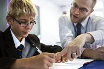 A teacher helps a pupil studying at Clevedon school, Clevedon. - Paul Box - 2010s,2013,Academies,Academy,adolescence,adolescent,adolescents,boy,boys,child,CHILDHOOD,children,class,classroom,classrooms,communicating,communication,conversation,conversations,dialogue,discourse,d