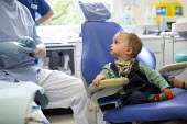 A young boy visiting the dentist, Bristol - Paul Box - 2010s,2013,BABIES,baby,boy,boys,chair,chairs,check,child,CHILDHOOD,children,cities,city,dental,dentist,dentistry,dentists,EARLY YEARS,employee,employees,Employment,examination,examining,face mask,hea,
