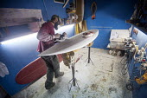 A surfboard shaper at work. - Paul Box - 2010s,2013,Board,by hand,craft,craftsman,dust,dusty,EBF,Economic,Economy,employee,employees,Employment,face mask,face masks,fiberglass,hazard,hazardous,hazards,health,job,jobs,lbr,male,man,mask,masked