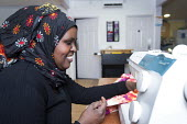 A Somali woman in a sewing class at the Wordsworth Community Centre, Southmead, Bristol - Paul Box - 2010s,2013,african,apparel,BAME,BAMEs,black,BME,bmes,centre,cities,city,clothes,clothing,communities,community,Diaspora,diversity,dress,EMOTION,EMOTIONAL,EMOTIONS,ethnic,ethnicity,FEMALE,foreign,forei