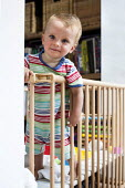 A young boy plays in his playpen. Bristol - Paul Box - 2010s,2013,babies,baby,boy,boys,CARE,carer,carers,child,childcare,CHILDHOOD,CHILDMINDING,children,cities,city,cot,cots,EARLY YEARS,EMOTION,EMOTIONAL,EMOTIONS,infancy,infant,infants,juvenile,juveniles,