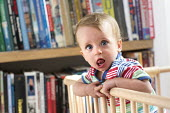 A young boy plays in his playpen. Bristol - Paul Box - 2010s,2013,babies,baby,BOOK,books,bookshelf,boy,boys,CARE,carer,carers,child,childcare,CHILDHOOD,CHILDMINDING,children,cities,city,cot,cots,EARLY YEARS,infancy,infant,infants,juvenile,juveniles,kid,ki