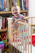 A young boy plays in his playpen. Bristol - Paul Box - ,2010s,2013,babies,baby,BOOK,books,bookshelf,boy,boys,CARE,carer,carers,child,childcare,CHILDHOOD,CHILDMINDING,children,cities,city,cot,cots,EARLY YEARS,EMOTION,EMOTIONAL,EMOTIONS,funny,happiness,happ