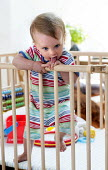 A young boy plays in his playpen. Bristol - Paul Box - 2010s,2013,babies,baby,boy,boys,CARE,carer,carers,child,childcare,CHILDHOOD,CHILDMINDING,children,cities,city,cot,cots,EARLY YEARS,infancy,infant,infants,juvenile,juveniles,kid,kids,male,out,people,pl