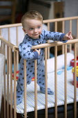 A one year old boy plays in his playpen. Bristol - Paul Box - ,2010s,2013,babies,baby,boy,boys,CARE,carer,carers,child,childcare,CHILDHOOD,CHILDMINDING,children,cities,city,cot,cots,EARLY YEARS,EMOTION,EMOTIONAL,EMOTIONS,infancy,infant,infants,juvenile,juveniles