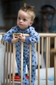 A one year old boy plays in his playpen. Bristol - Paul Box - ,2010s,2013,babies,baby,boy,boys,CARE,carer,carers,child,childcare,CHILDHOOD,CHILDMINDING,children,cities,city,cot,cots,EARLY YEARS,infancy,infant,infants,juvenile,juveniles,kid,kids,male,people,playp