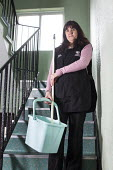 A cleaner employed by Cardiff council, working at a block of flats, Cardiff. - Paul Box - 2010s,2013,block,blocks,bucket,buckets,cleaner,cleaners,cleaning,cleansing,council,Council Services,Council Services,EARNINGS,employee,employees,Employment,EQUALITY,FEMALE,flat,flats,hall,High Rise,In