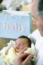 A newborn asleep, with a present behind them. - Paul Box - ,2000s,2006,all-in-one,all-in-ones,asleep,babies,baby,babygrow,babygrows,birthday,birthdays,blanket,blankets,Bodysuit,Bodysuits,boy,boys,care,carer,carers,caring,carries,carry,carrying,child,childcare