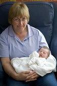 A newborn asleep, being held by their grandmother. - Paul Box - 04-06-2006