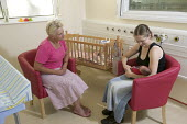 Counselor discussing care with a new mother. Neonatal Intensive Care Unit, Southmead Hospital, Bristol - Paul Box - 2000s,2006,adult,adults,advice,ADVISE,ADVISER,advisers,advising,advisor,advisors,Assistant,ASSISTANTS,babies,baby,bed,beds,birth,Bristol,care,carer,carers,caring,Changing,child,child care,childcare,CH