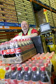 A stock picker working at Coca Cola & Cadbury Schweppes Distribution Center, London. - Paul Box - 2000s,2005,and,Beverage,Beverages,bottle,bottles,bulk,business,businesses,Cadbury,Cadbury's,can,cans,centre,cities,city,Coca Cola,Coca-Cola,coke,Company,COMPUTE,computer,computers,COMPUTING,confection