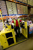 A stock picker working at Coca Cola & Cadbury Schweppes Distribution Center, London. - Paul Box - 2000s,2005,and,Beverage,Beverages,bottle,bottles,bulk,business,businesses,Cadbury,Cadbury's,can,cans,centre,cities,city,Coca Cola,Coca-Cola,coke,Company,confectionery,distributing,Distribution,drink,d