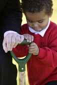 Woodland Trust's Tree For All, a children tree-planting project taking place at Fair Furlong Primary School, Bristol. - Paul Box - 2000s,2005,adult,adults,BAME,BAMEs,black,BME,BME Black minority ethnic,bmes,boy,boys,charitable,charities,charity,child,CHILDHOOD,children,cities,city,conservation,country,countryside,cultural,dig,dig