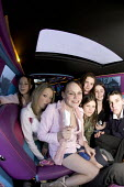 A group of teenagers, riding in a limousine. - Paul Box - 2000s,2005,adolescence,adolescent,adolescents,AUTO,AUTOMOBILE,AUTOMOBILES,AUTOMOTIVE,boy,boys,car,cars,child,CHILDHOOD,children,EMOTION,EMOTIONAL,EMOTIONS,female,females,girl,girls,glasses,group,group