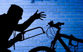A thief, trying to steal a bicycle. - Paul Box - ,2000s,2005,bicycle,bicycles,BICYCLING,Bicyclist,Bicyclists,bike,bikes,Brick Wall,Cable,cities,city,CLJ,CLJ crime,crime,crime prevention,crimes,criminal,criminals,CYCLE,cycles,CYCLING,Cyclist,Cyclists