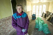 A resident returning to her flood damaged home in Tewkesbury, four months after the floods in Gloucestershire. - Paul Box - 2000s,2007,2008,accommodation,age,ageing population,apparel,BAD,BAG,bags,bin,bin bag,bins,brick,BRICKS,Brickwork,building,buildings,Cleaning,cleansing,clothes,clothing,coat,coats,damage,damaged,damp,d