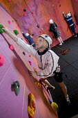 Pupils rock climbing, as part of the Physical Education and School Sport (PESS) programme, which is being initiated within Hareclive Primary School. - Paul Box - (bulge),(bulges),(incut),(incuts),(PESS),2000s,2005,and,Art,artificial,ascend,ascended,ascending,belay,bolt-on,boy,boys,child,CHILDHOOD,children,cities,city,class,classes,cliff,cliffs,climb,climbed,cl