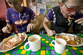 Two cyclists eating a english breakfast, before cycling in Snowdonia National Park. - Paul Box - 2000s,2005,and,baked,bean,beans,BICYCLE,BICYCLES,BICYCLING,BICYCLIST,Bicyclists,big,BIKE,BIKES,breakfast,breakfasts,brown,browns,cooked,cup,cups,CYCLE,cycles,Cycling,cyclist,cyclists,eat,eating,egg,eg