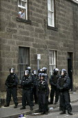 G8 protest demonstrations in Edinburgh on Monday 4th of July. A resident looks out on her street full of riot police. - Paul Box - 04-07-2005