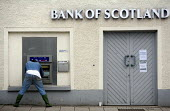 The Bank of Scotland closes for the day . A man gets money from the cash machine. - Paul Box - 06-07-2005