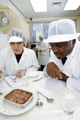 Food and other products being examined and compared in an laboratory environment. At the food and drink research centre, Camden Chorleywood Food Research Association (CCFRA). - Paul Box - 2000s,2006,and,BAME,BAMEs,bme,BME Black minority ethnic,bmes,centre,centres,check,checking,coat,coats,communicating,communication,compare,compared,comparing,conversation,conversations,dialogue,discour