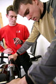 A personal trainer, one-to-one coaching their client. - Paul Box - &,2000s,2007,adult,adults,Aerobic,and,assist,assisting,bicycle,bicycles,BICYCLING,Bicyclist,Bicyclists,bike,bikes,bodybuilding,cardio,cardio vascular,Cardiovascular,cities,city,client,clients,clock,cl