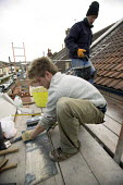 A builder works on a roof of a victorian terraced house in Bristol. - Paul Box - 02-03-2008