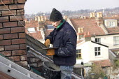A builder works on a roof of a victorian terraced house in Bristol. - Paul Box - 2000s,2008,bricklaying,builder,builders,Building Worker,chimney,chimneys,cities,city,Construction Industry,EBF economy,height,high,house,houses,job,jobs,LAB LBR work,ladder,ladders,maintaining,mainten