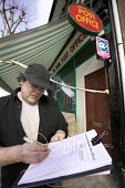 A local resident signs a petition for prevent the proposed closure of a local post office. Sefton post office, Bristol. The petition must be signed outside the post office . If the petition is signed... - Paul Box - 02-03-2008