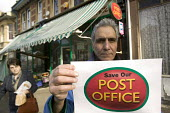 The shop keeper holds up a save our post office sign.. Sefton Park post office, Bristol. The petition must be signed out side the post office . If the petition is signed inside post offices could lose... - Paul Box - 2000s,2008,activist,activists,branch,BRANCHES,campaign,campaigner,campaigners,campaigning,CAMPAIGNS,cities,city,closed,closing,closure,closures,communicating,communication,cuts,DEMONSTRATING,demonstra
