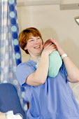 A midwife and a newborn in a postnatal ward. At South Warwickshire General Hospital. - Paul Box - 20-02-2008