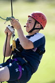 Young people taking part in an activity week at PGL Osmington Bay Centre in Weymouth. - Paul Box - 2000s,2007,Abseil,Abseiling,activities,activity,adolescence,adolescent,adolescents,adventure,adventurecourse,ascend,ascended,ascending,Bay,boy,boys,camp,camps,child,CHILDHOOD,children,Climbing,confu