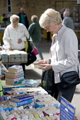 A bookstall at a street market, in Preston. - Paul Box - 2000s,2005,adult,adults,age,ageing population,area,areas,book,books,bought,browse,browsing,buy,buyer,buyers,buying,charitable,charities,charity,cities,city,commodities,commodity,consumer,Consumers,cus