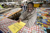 A religious bookstall at a street market, in Preston. The Synoptic Gospels - Paul Box - ,2000s,2005,area,areas,BAME,BAMEs,bible,biblical quote,biblical quotes,Black,BME,bmes,book,books,bought,browse,browsing,buy,buyer,buyers,buying,charitable,charities,charity,christian,christianity,chri