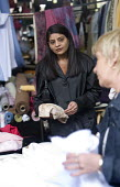 A woman at a fabric stall at a street market, in Preston. - Paul Box - 2000s,2005,area,areas,asian,asians,attention,attentive,BAME,BAMEs,Black,BME,bmes,bought,browse,browsing,buy,buyer,buyers,buying,charitable,charities,charity,cities,city,clothes,commodities,commodity,c