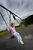 A young girl playing on a swing, in a playground. - Paul Box - 25-06-2005