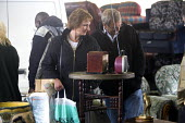 A couple browsing at a car boot sale. - Paul Box - 2000s,2005,adult,adults,AUTO,AUTOMOBILE,AUTOMOBILES,AUTOMOTIVE,bag,bags,boot,bought,browse,browsing,buy,buyer,buyers,buying,car,CARS,chair,chairs,cities,city,commodities,commodity,communicating,commun