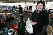 A woman browsing at a car boot sale. - Paul Box - 2000s,2005,AUTO,AUTOMOBILE,AUTOMOBILES,AUTOMOTIVE,bag,bags,boot,bought,browse,browsing,buy,buyer,buyers,buying,car,CARS,cities,city,commodities,commodity,consumer,Consumers,customer,customers,EBF,Econ