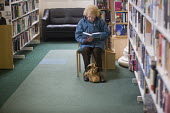 A woman reading at Preston Library. - Paul Box - 2000s,2005,ace culture,age,ageing population,book,books,browse,browsing,collection,collections,elderly,FEMALE,glasses,handbag,handbags,information,learn,learning,LFL Leisure,libraries,library,novel,no