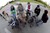 A group of friends on their BMXs, Llanlishen Skate Park, Cardiff - Paul Box - 2000s,2005,adolescence,adolescent,adolescents,basketball,bicycle,bicycles,BICYCLING,Bicyclist,Bicyclists,bike,bikes,BMX,BMXs,boy,boys,cap,caps,child,CHILDHOOD,children,communicating,communication,conv
