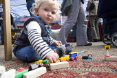A farmers' market in Butetown, Cardiff. A child of a stallholder playing with toys. - Paul Box - 22-05-2005