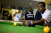 Teenagers playing snooker at Butetown Youth Centre, in Cardiff. - Paul Box - ,2000s,2005,adolescence,adolescent,adolescents,ball,balls,BME Black minority ethnic,boy,boys,centre,centres,child,CHILDHOOD,children,cities,city,club,clubs,communities,community,Council Services,Counc