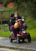 A woman with her shopping rides the pavement on a mobility scooter, Witney, Oxfordshire. - Paul Box - 09-09-2008